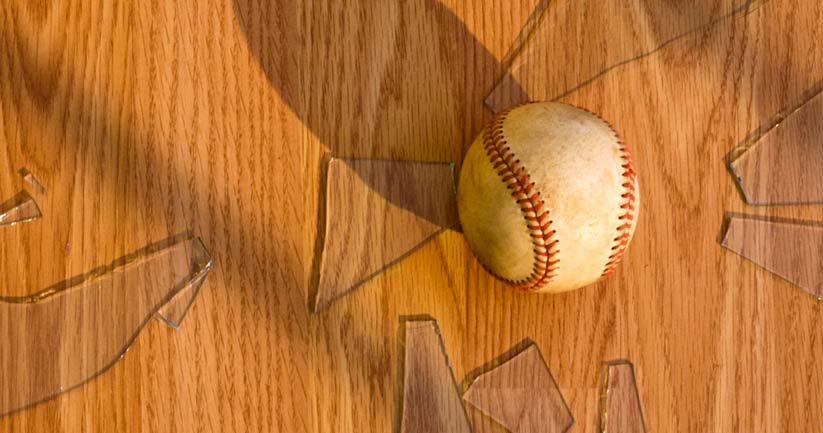 Baseball laying on the floor with broken glass
