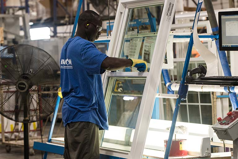 Champion employee working on final assembly of window