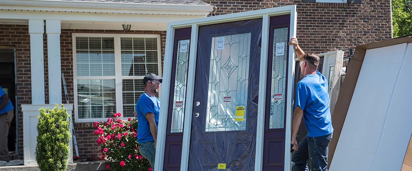 Champion installers carrying door to be installed