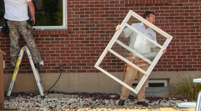 Champion installer removing old window frame from home